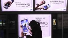A woman walks banners advertising Samsung Electronics' Galaxy Note III at a subway station in Seoul, South Korea, Thursday, Dec. 12, 2013. (Ahn Young-joon/AP)