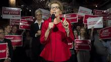 Ontario premier Kathleen Wynne, right, speaks as her wife Jane Rounthwaite looks on during an Ontario Liberal Party rally in Toronto on May 2. (Darren Calabrese/THE CANADIAN PRESS)