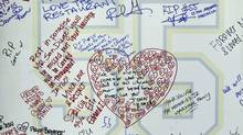 Messages are written on a board emblazoned with a No. 55 during a public memorial service for late football player Junior Seau, who committed suicide last May (Gregory Bull/The Associated Press)