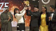 Maggie MacDonnell raises the Global Teacher Prize with one of her students while standing next to Dubai ruler Sheikh Mohammed bin Rashid Al Maktoum, in Dubai, United Arab Emirates. (Martin Dokoupil/The Associated Press)
