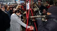 Shoppers carry holiday purchases as a band from the Salvation Army plays carols in New York's Herald Square on December 20, 2003. (CHIP EAST/REUTERS)