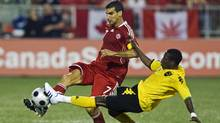 Canada's Paul Stalteri battles for the ball with Jamaica's Demar Phillips (R) during the first half of their 2010 FIFA World Cup Qualifiers match in Toronto, August 20, 2008. (Reuters)
