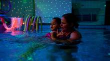 Ms. Yoshei, a hydrotherapist, uses lights together with water as she treats an autistic child in a swimming pool. She leaves work at 3:30 to pick up her girls and be with them at home. (Heidi Levine/Sipa Press)