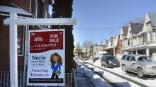 A real estate sign sits on the front lawn of a home on in Toronto in this file photo. (Fred Lum/The Globe and Mail)