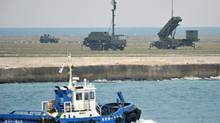 A fishing boat sails by a ground-based Patriot Advanced Capability-3 interceptor, right, and other vehicles deployed to prepare for North Korea's planned launch of a long-range rocket, at a port in Ishigaki on Ishigaki Island, Okinawa Prefecture, southwestern Japan, Dec. 10, 2012. (Kyodo News/AP)