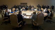 British Prime Minister David Cameron and German Chancellor Angela Merkel, front from left, share a word during a G8 working session with other world leaders during the G8 Summit at the Deerhurst Resort in Hunstville, Ont., Saturday. (Guido Bergmann/AP Photo)