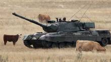 A Leopard C2 tank rides across a field at CFB Wainwright during a training exercise. The base commander, Major David Yurczyszyn, has been charged with drunkenness and sexual assault. (Ryan Jackson/CP)