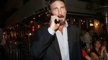 Anti-virus software founder John McAfee talks on his mobile phone as he walks on Ocean Drive in the South Beach area of Miami Beach, Fla., on his way to dinner Dec 12, 2012. (Alan Diaz/AP)