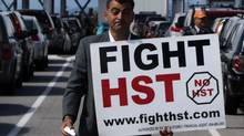 Local anti-HST organizer Eddie Petrossian carries a sign as he walks to meet former British Columbia premier Bill Vander Zalm before boarding a ferry in Tsawwassen, B.C., on Wednesday June 30, 2010, to deliver anti-HST petitions to Elections B.C. in Victoria. (Darryl Dyck/ The Canadian Press/Darryl Dyck/ The Canadian Press)