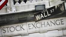 A Wall Street sign is seen outside the New York Stock Exchange in this file photo. (Mark Lennihan/AP)