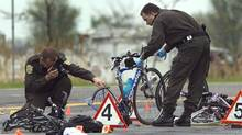 Police examine the scene where a pickup truck plowed into a group of cyclists Friday, May 14, 2010, in Rougemont, Quebec, south of Montreal. (Ryan Remiorz/THE CANADIAN PRESS/Ryan Remiorz)