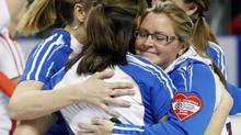 British Columbia skip Kelly Scott hugs her teammates after they defeated Team Canada (MARK BLINCH/REUTERS)