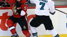 Ottawa Senators' Derek Grant (57) and San Jose Sharks' Brad Stuart battle for a loose puck along the boards during second period NHL hockey action in Ottawa Sunday October 27, 2013. (FRED CHARTRAND/THE CANADIAN PRESS)