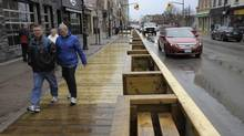 Pedestrian walk on a a wooden boardwalk past a host of new shops and restaurants, including poutine, raw organic, gastronomie, indian, middle eastern, and Italian to name a few, are evident on Dunlop street in downtown Barrie on April 19, 2013. (J.P. MOCZULSKI for The Globe and Mail)