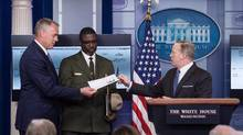 White House spokesman Sean Spicer hands Interior Secretary Ryan Zinke, left, the first quarter check of US President Donald Trump's salary which he donated to the National Park Service. (NICHOLAS KAMM/AFP/Getty Images)