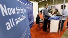 Exhibitors speak with visitors a job fair in Toronto in this April 3, 2014 file photo. (Aaron Harris/Reuters)