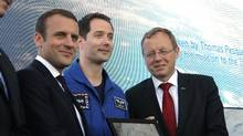 French President Emmanuel Macron, left, poses with French astronaut Thomas Pesquet and European Space Agency (ESA) Director General, Johann-Dietrich Woerner, right, while visiting the Paris Air Show in Le Bourget, north of Paris, Monday, June 19, 2017. Macron's centrist Republic on the Move (LREM) party and its centre-right Modem ally won 350 out of 577 seats in the lower house elections. (Michel Euler/AP)