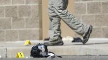 Yellow markers sit next to evidence, including a gas mask, as police investigate the scene outside the Century 16 movie theater east of the Aurora Mall in Aurora, Colo. on Friday, July 20, 2012. (David Zalubowski/AP)