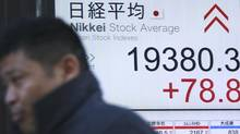 A man walks past an electronic stock board showing Nikkei stock index at a securities firm in Tokyo, Wednesday, Jan. 11, 2017. Asian shares were mostly higher Wednesday morning on the back of a strengthening U.S. dollar and quiet trading ahead of remarks by president-elect Donald Trump. (Shuji Kajiyama/AP)
