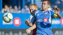 Montreal Impact's Davy Arnaud, right, tackles Chicago Fire's Jeff Larentowicz during first half MLS action in Montreal, Saturday, April 27, 2013. (Graham Hughes/THE CANADIAN PRESS)