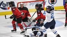 Finland's Noora Tulus (24) and Emma Nuutinen (22) celebrate the winning goal over Canada in the IIHF Ice Hockey Women's World Championship preliminary round game in Plymouth, Mich., April 1, 2017. (Jason Kryk/THE CANADIAN PRESS)