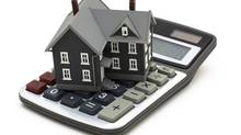 A small model of a house sits on calculator. (Karen Roach/iStockphoto)