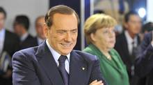 Italy's Prime Minister Silvio Berlusconi walks past Germany's Chancellor Angela Merkel before a working session at the G20 Summit of major world economies in Cannes November 3, 2011. (TOBY MELVILLE/REUTERS)