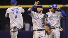 Toronto Blue Jays right fielder Jose Bautista (19), shortstop Jose Reyes (7) and teammates celebrate after defeating the Tampa Bay Rays 7-4 at Tropicana Field. (Kim Klement/USA Today Sports)
