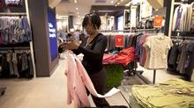 Sales staff Andrea Barnswell at work at the Reitman's retail location at the Toronto Eaton Centre in this March, 2011 file photo. The country's largest specialty apparel chain faced strong headwinds last year, ranging from high cotton prices and bad shopping weather, to less discretionary spending among Canadians. (Moe Doiron/The Globe and Mail/Moe Doiron/The Globe and Mail)
