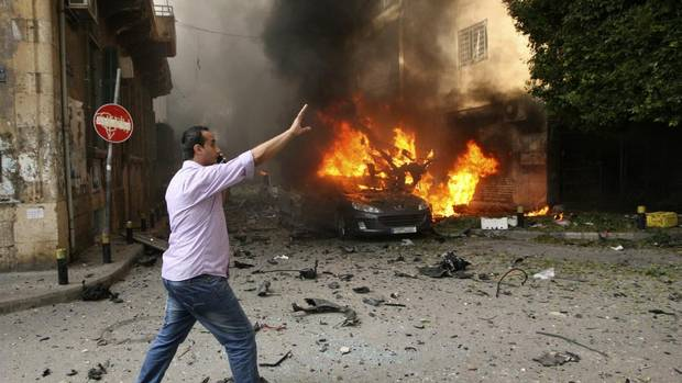 A man reacts near a burning car at the site of an explosion in Ashafriyeh, central Beirut, October 19, 2012. At least eight people were killed and 78 wounded by a bomb that exploded in central Beirut on Friday, the state news agency said. (STRINGER/REUTERS)