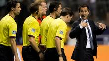Vancouver Whitecaps head coach Martin Rennie, right, speaks with the officials as he leaves the pitch after losing 2-0 to FC Dallas during an MLS soccer game in Vancouver, B.C., on Wednesday August 15, 2012. (The Canadian Press)