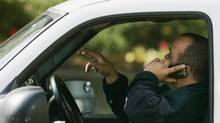 A driver talks on his phone while driving through downtown Toronto October 26, 2009. (REUTERS)