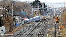 Crews investigate and prepare to remove the wreckage on Feb. 27, 2012, after a VIA train derailed en route from Niagara Falls to Toronto. (Peter Power/The Globe and Mail)