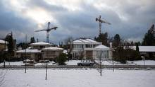Cranes rise above homes in front a construction site in Vancouver in December, 2016. (Ben Nelms/Bloomberg)