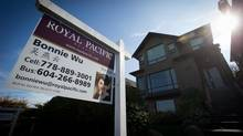 A for sale sign is seen on the lawn of a house listed for sale for $3.16-million in the Dunbar neighbourhood of Vancouver, B.C., on Thursday October 9, 2014. (DARRYL DYCK For The Globe and Mail)