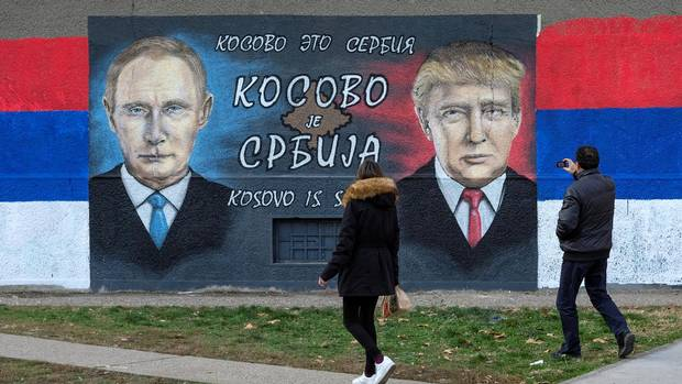 A man takes pictures of a mural of Russian President Vladimir Putin and U.S. President Donald Trump in Belgrade in December.