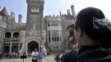 Chinese tourists photograph Casa Loma in Toronto, August 6 , 2011. The growth in non-American tourism to Canada has been driven by strong gains in travel from China, where a growing middle class now has the means to see the world. (J.P. MOCZULSKI For The Globe and Mail)