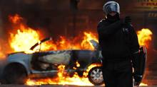 A riot police officer directs his colleagues to clear people away from a burning car in Clarence Road in Hackney on August 8, 2011 in London, England. Pockets of rioting and looting continues to take place in various boroughs of London (Dan Istitene/Dan Istitene/Getty Images)