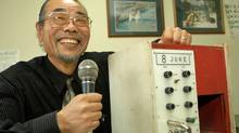Holding a microphone, Daisuke Inoue grins as he shows his 1971 invention the 8-Juke, a red and white wooden box that combined microphone, amplifier and an eight-track tape player, at his office in Osaka, western Japan, Dec. 6, 2002. Back when Inoue was a youngster banging drums with a local lounge band, he didn't think his invention would amount to much. He certainly had no idea of applying for a patent. But three decades later, karaoke is a household word and Inoue hardly sees a dime. (KOJI SASAHARA)
