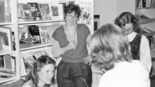 Judy Sarick at a book signing with author Judy Blume (Sarick is standing with her hand on hip, facing the camera, and Blume is seated). (Courtesy of the Family)