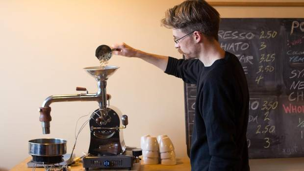 Rogue Wave Coffee co-owner David Walsh pours green beans into a coffee roaster, used to roast samples.