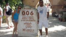 Tourists get their picture taken next to a slab of stone counting down the days until Dec. 21, 2012 at the Xcaret theme park in Playa del Carmen, Mexico, Saturday, Dec. 15, 2012. (Israel Leal/AP)