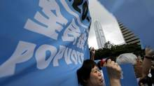 "Pro-democracy supporters raise banners that read ""eferendum"" during a kickoff ceremony for a referendum on democracy in Hong Kong on June 20, 2014. (VINCENT YU/ASSOCIATED PRESS)"
