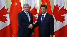 Canadian Prime Minister Stephen Harper poses with Chinese President Xi Jinping for a photo at the Great Hall of the People in Beijing, Sunday, Nov. 9, 2014 ahead of the Asia-Pacific Economic Cooperation forum. (Petar Kujundzic/AP)