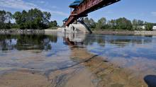 Traces of the oil spill that occurred after a train explosion in Lac-Megantic, Que., are seen about 70 kilometres downstream under a pedestrian bridge in Saint-Georges, Que. (JACQUES BOISSINOT/THE CANADIAN PRESS)