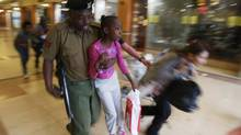 A soldier carries a child to safety as armed police hunt gunmen who went on a shooting spree at Westgate mall in Nairobi, September 21, 2013. (GORAN TOMASEVIC/REUTERS)