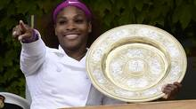 Serena Williams of the U.S. holds her trophy as she stands on the clubhouse balcony after defeating Agnieszka Radwanska of Poland in their women's final tennis match at the Wimbledon tennis championships in London July 7, 2012. (DYLAN MARTINEZ/REUTERS)