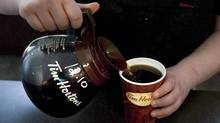 "As the wave of anonymous coffee benefactors spreads to more Tim Hortons locations, spokeswoman Michelle Robichaud says that as ""brilliant"" as this is, it is not Tim Hortons's doing. A cup of coffee is poured in Toronto on May 14 2010. (Chris Young/THE CANADIAN PRESS)"