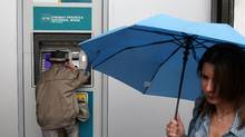 A woman with an umbrella walks past a man using an ATM of the National Bank of Greece in Athens, Friday, May 18, 2012. (Thanassis Stavrakis/AP)