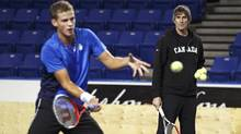Team Canada Davis Cup member Vasek Pospisil returns a shot as coach Martin Laurendeau looks on during a training session at the University of B.C. on Feb. 6, 2012. (Jeff Vinnick for The Globe and Mail/Jeff Vinnick for The Globe and Mail)